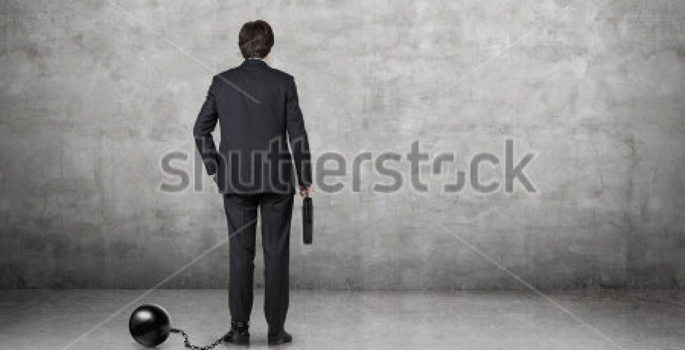 stock-photo-ball-and-chain-restraining-a-businessman-freedom-of-decision-making-206476459