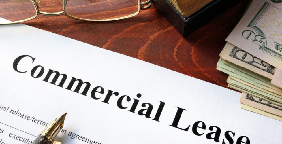 60527095 - commercial lease agreement with money on a table.
